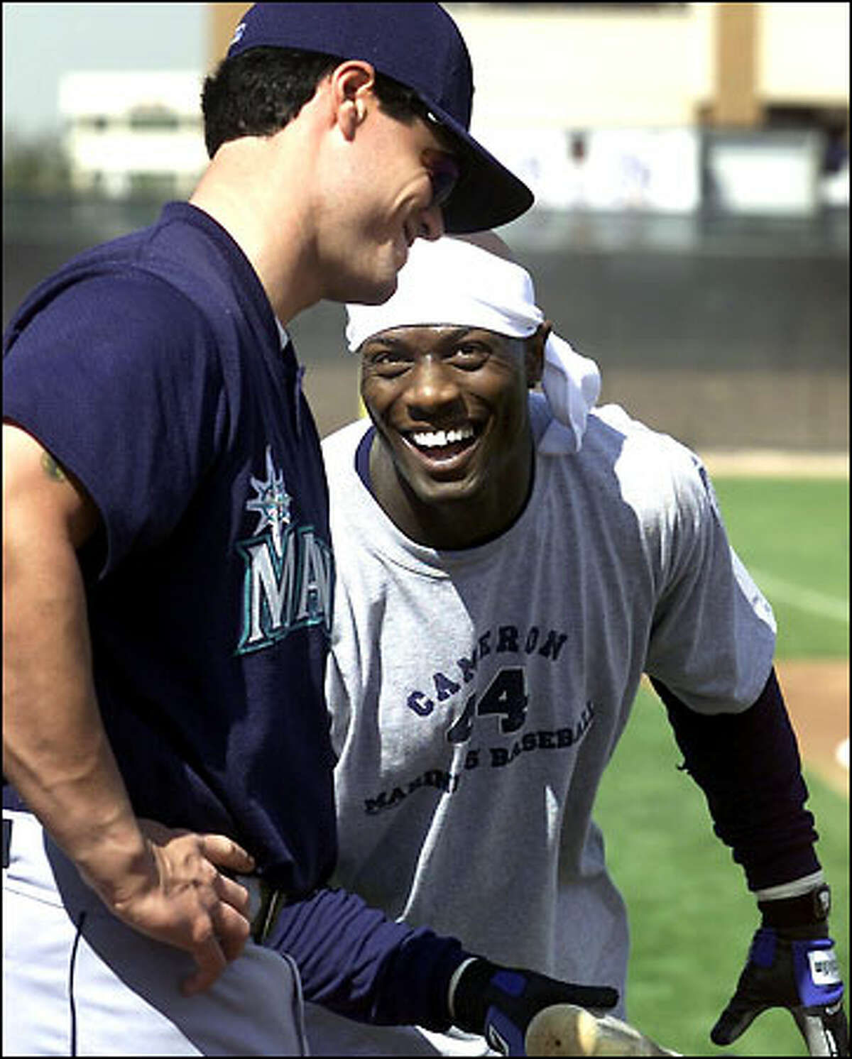 Mariners center fielder Mike Cameron jokes with new catcher Ben Davis during a break in batting practice at the team's spring training camp.