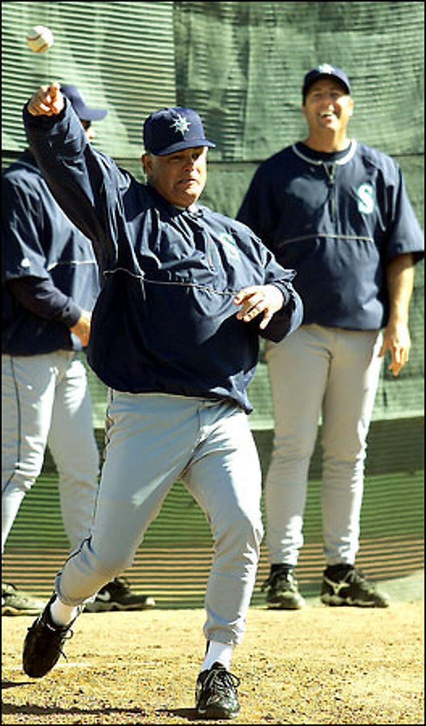 Lou Piniella shows off his pitching form, as pitching coach Bryan Price gets a good laugh.