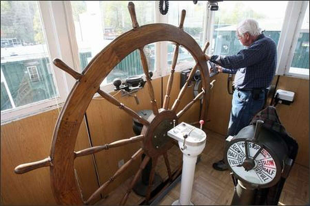Captain Joe Linehan programs his electronic GPS while resting his free hand on the seven-foot steering wheel of the 161-foot stern-wheeler the Alaska Queen while the boat enters its final phase of restoration at the Foss Maritime shipyard in Seattle, Wash., Tuesday April 3, 2007. The ship is owned by Alaska Travel Adventures.