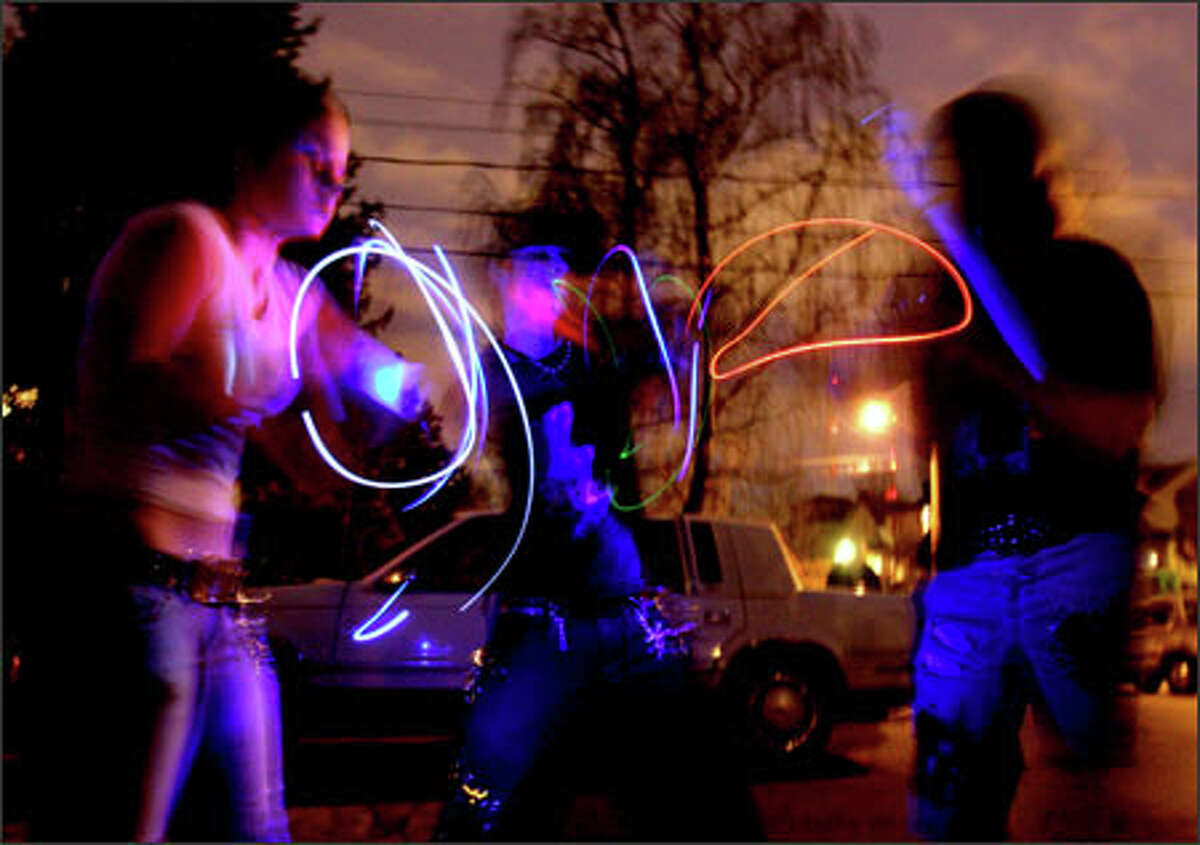 Near the scene of the Capitol Hill shootings, Giggles, 16, left, and Nemesis, 19, center, do a light show on the street as a tribute to