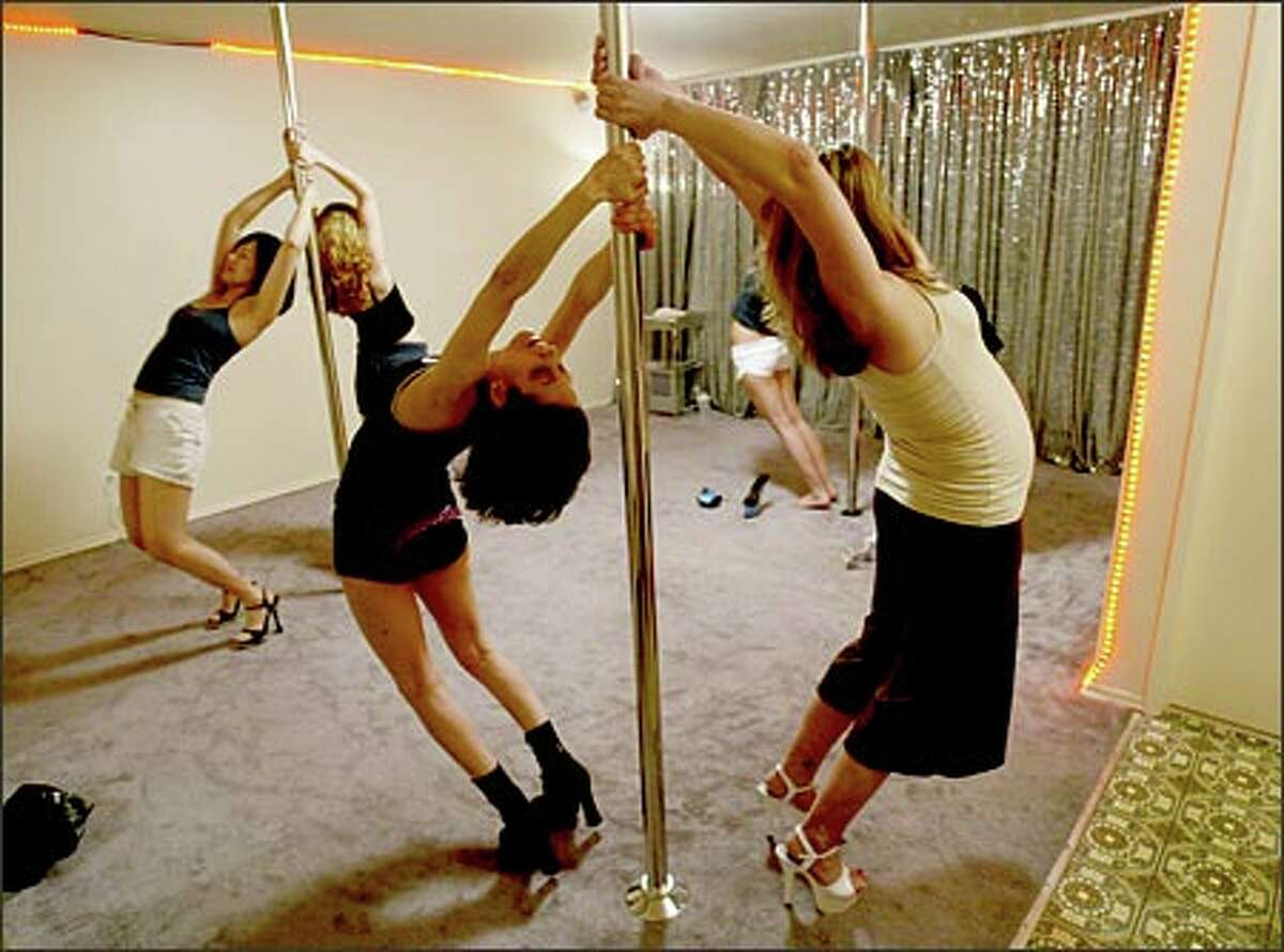 Krisha CatZen, center front, leads her pole-dancing class in stretching exercises. The former go-go dancer says,