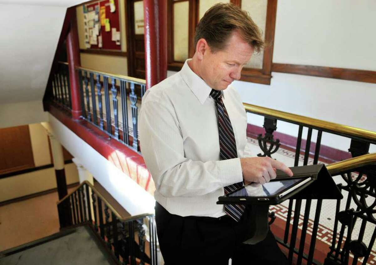Watervliet Mayor Michael P. Manning checks his iPad in the stairwell of City Hall. About 12 city employees have the tablets as part of effort to reduce paper and improve government workability. (John Carl D'Annibale / Times Union)