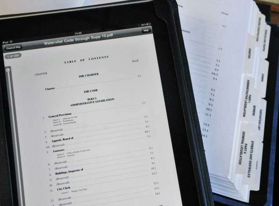 An iPad with a PDF file of the Watervliet Code atop a copy of its paper counterpart at City Hall. About 12 city employees have the tablets as part of effort to reduce paper and improve government workability.   (John Carl D'Annibale / Times Union) Photo: John Carl D'Annibale / 00012359A