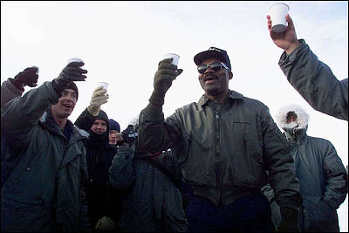 In nautical tradition, the oldest and youngest member of the Polar Star crew rang a bell and gave a toast for the New Year. On the left are Seaman apprentice Douglass Adams, 17, the youngest (toasting with Pepsi), and Master Chief James Parks, 49. At the time it was approximately -14 degrees with the wind chill factor.
