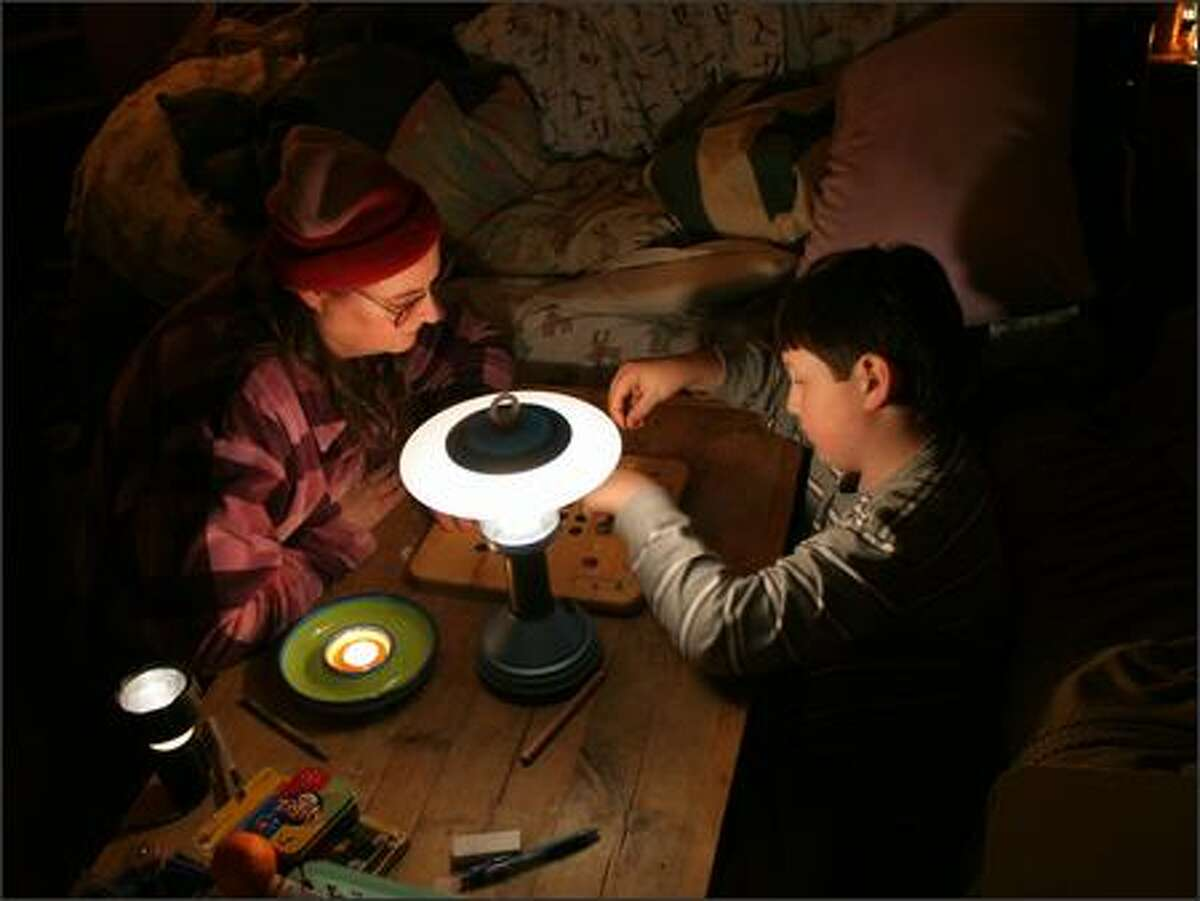 Lisa Anne Jasper and son Jeffrey try playing a game of Mancala by candle and battery-powered lamp during the storm. (Submitted by Mike Baxter)
