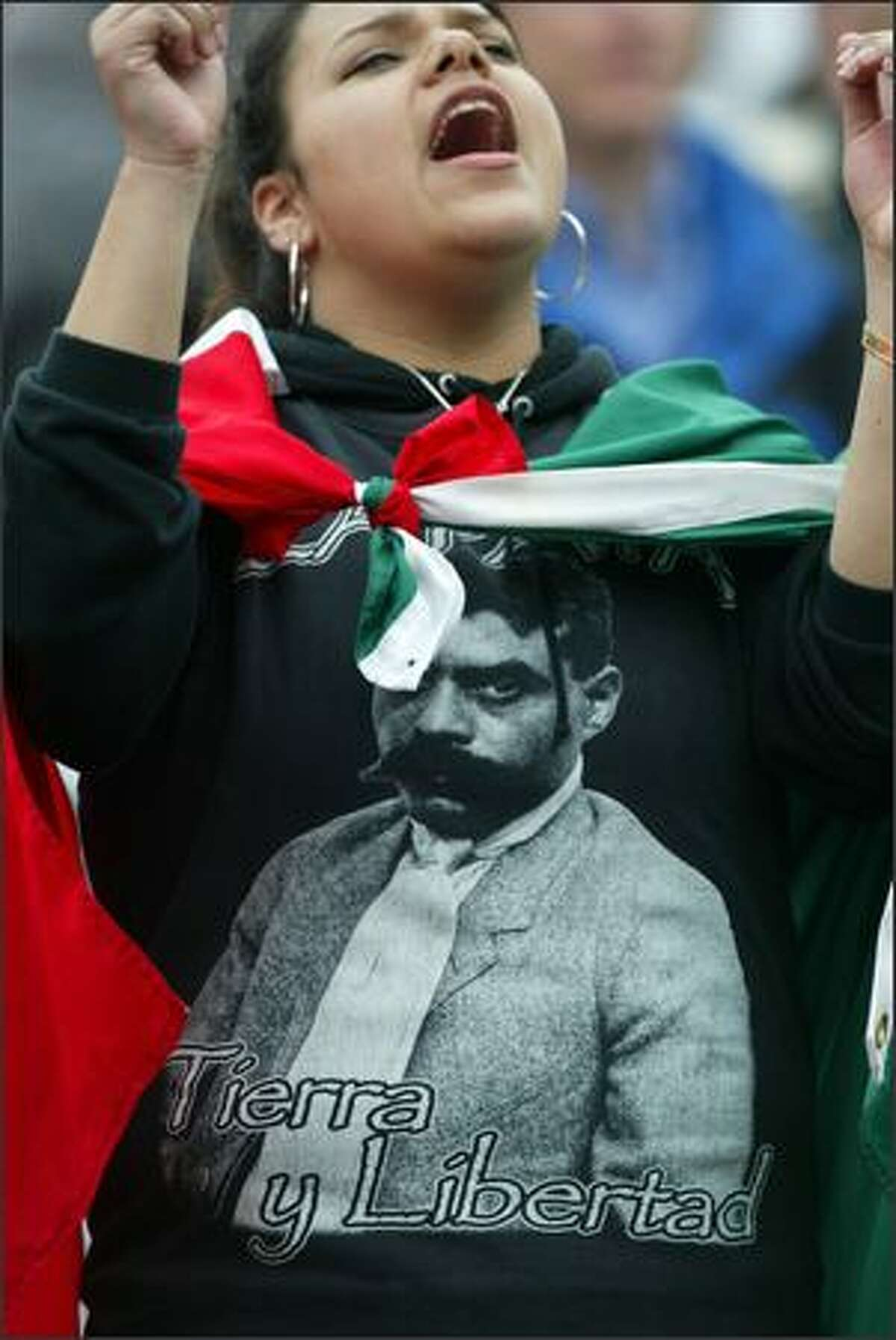 Wearing a shirt bearing the image of Mexican revolutionary Emiliano Zapata and wrapped in a Mexican flag, Elizabeth Del Real, 17, from Guadalahara, Mexico cheers during an immigration reform rally at the Seattle Center on May 1, 2007. Del Real now lives in Lynnwood, Wash.