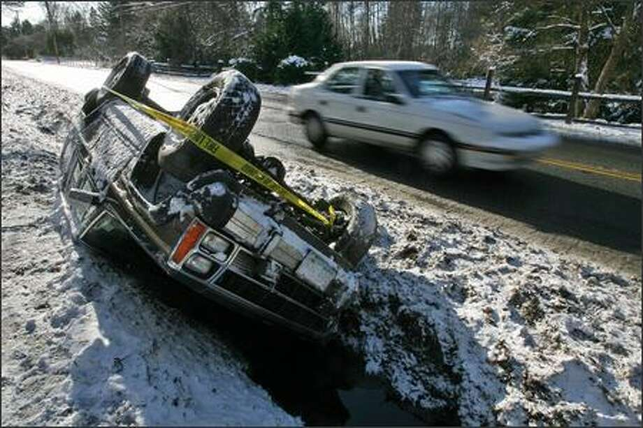 Snow and icy conditions on Vashon Island proved too much for at least one driver, whose vehicle came to rest upside-down in a 3-foot ditch on the island's main highway Thursday. Roads across Western Washington remained treacherous the day after a snowstorm swept through the region. Photo: Mike Urban, Seattle Post-Intelligencer