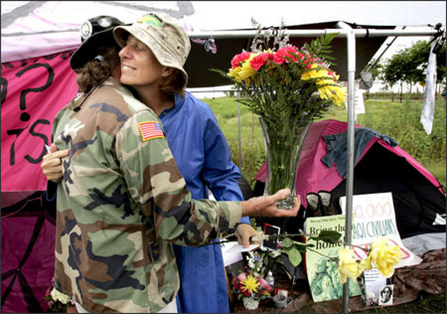 Cindy Sheehan, right, gets a hug from fellow protester Bill Mitchell as he delivers flowers sent to the roadside camp in Crawford, Texas. Photo: /Associated Press / AP