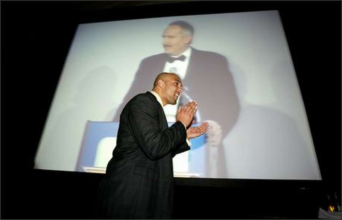 Washington State defensive end Mkristo Bruce is introduced by master of ceremonies Steve Raible, shown on big screen.