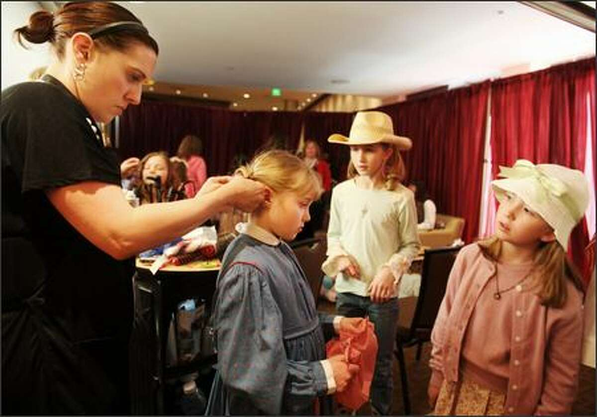 Sarah Jones (center) gets her hair done by Audry Lambert of Soma Salon and Day Spa in Edmonds as she draws interest from Mary Armintrout (second from right) and Mackenzie Taylor (right) prior to the start of the American Girl fashion show to benefit Seattle Children's Hospital held at the Westin Hotel in Bellevue on Friday March 16, 2007.