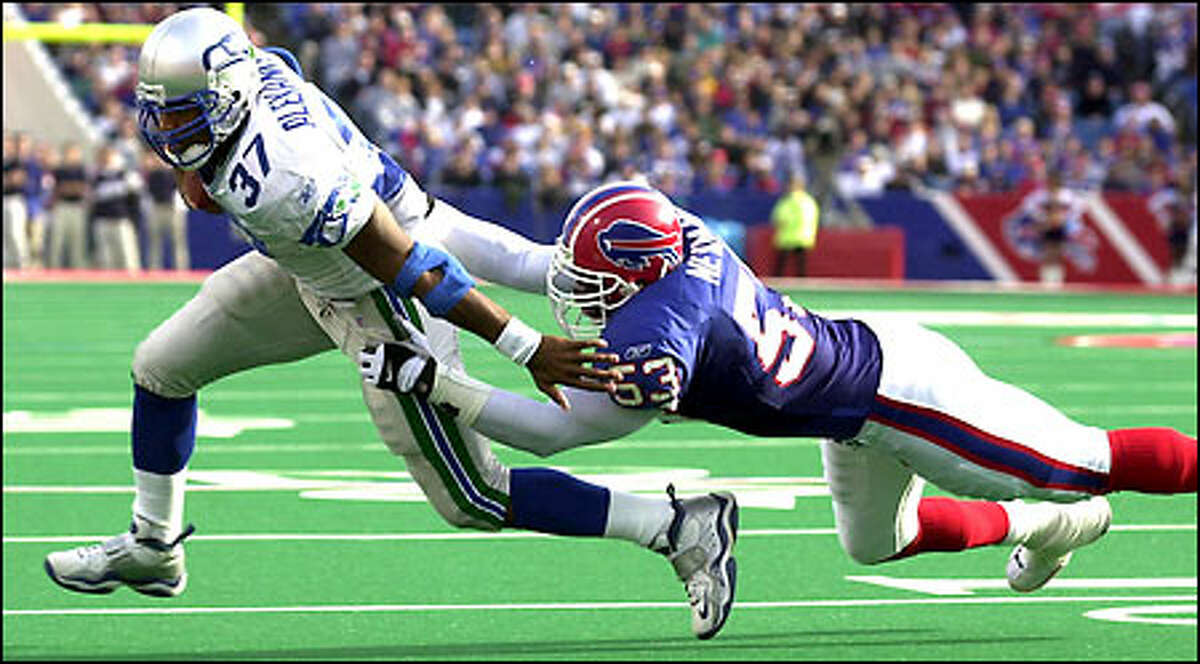 Seahawks running back Shaun Alexander, who carried 25 times for 93 yards and scored his 10th rushing touchdown of the season, is dragged down by Bills linebacker Keith Newman during the first quarter.