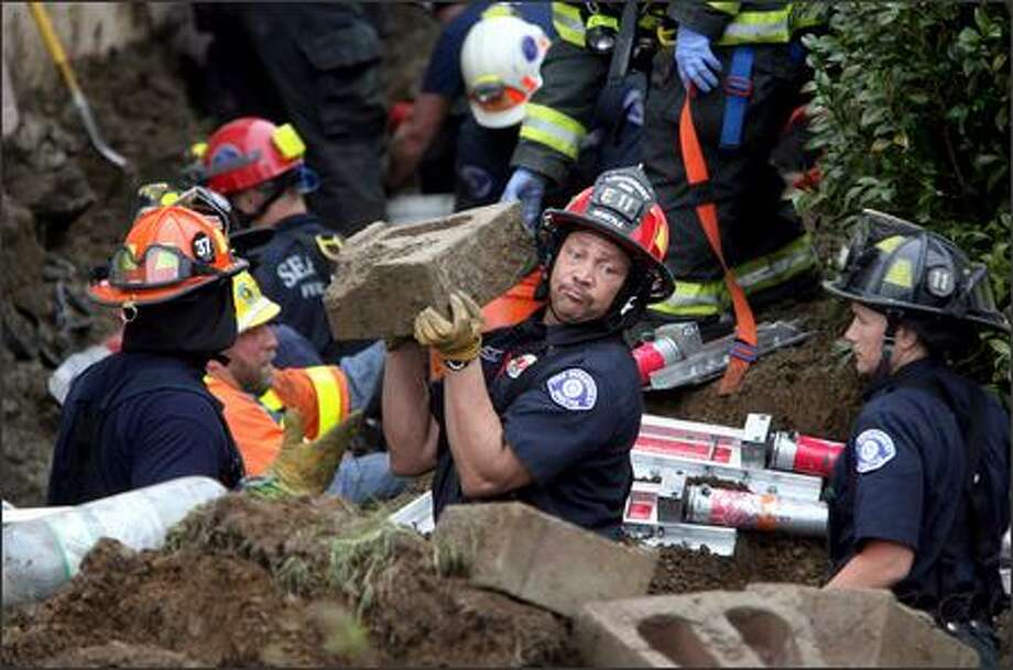 Seattle Fire Department Lt. Jerry Willis, with Engine 11, and other rescue workers form a bucket brigade in their battle to save a man buried Friday in a trench collapse in White Center. Photo: Mike Urban, Seattle Post-Intelligencer