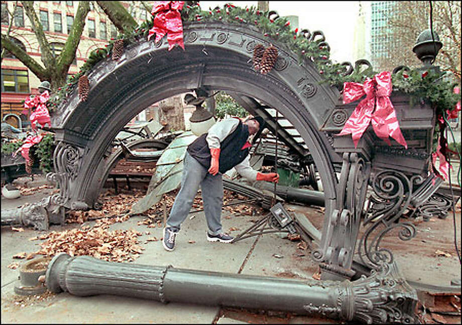 Larry Henderson of Seattle's Department of Parks and Recreation picks up pieces of the historic Pioneer Square pergola, which was destroyed by a truck. Photo: Renee C. Byer, Seattle Post-Intelligencer