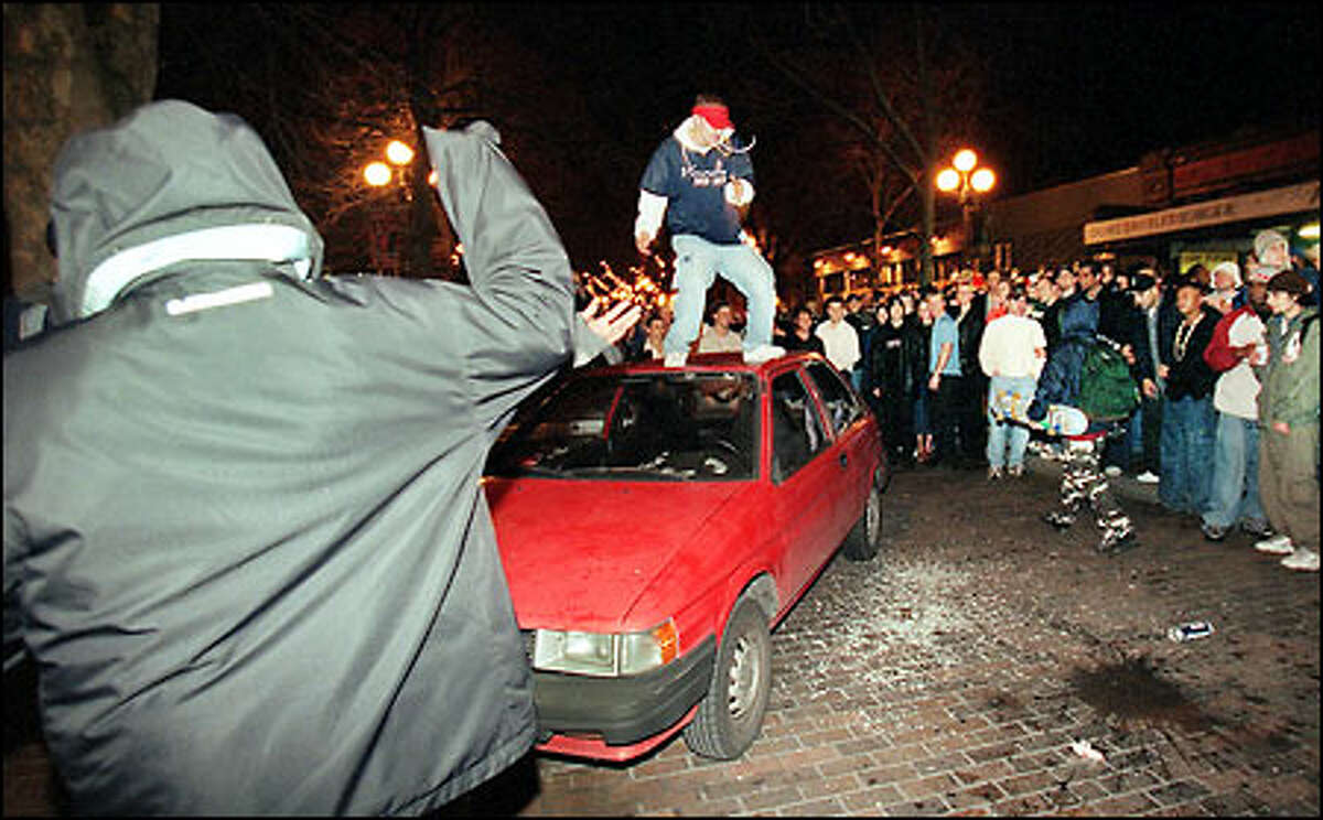 A crowd watches while a man leaps atop a car as Mardi Gras celebrations in Pioneer Square turned ugly.