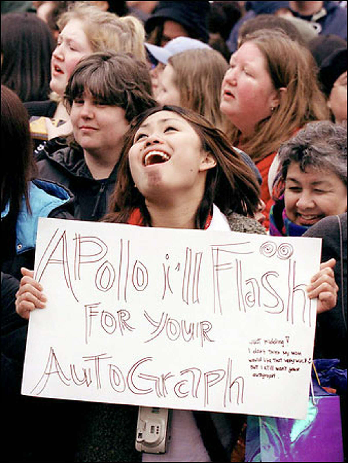 Roseann Cabrito, 15, of Seattle waves a sign in hopes to get an autograph from Apolo Ohno during a rally in his honor at Westlake Park.