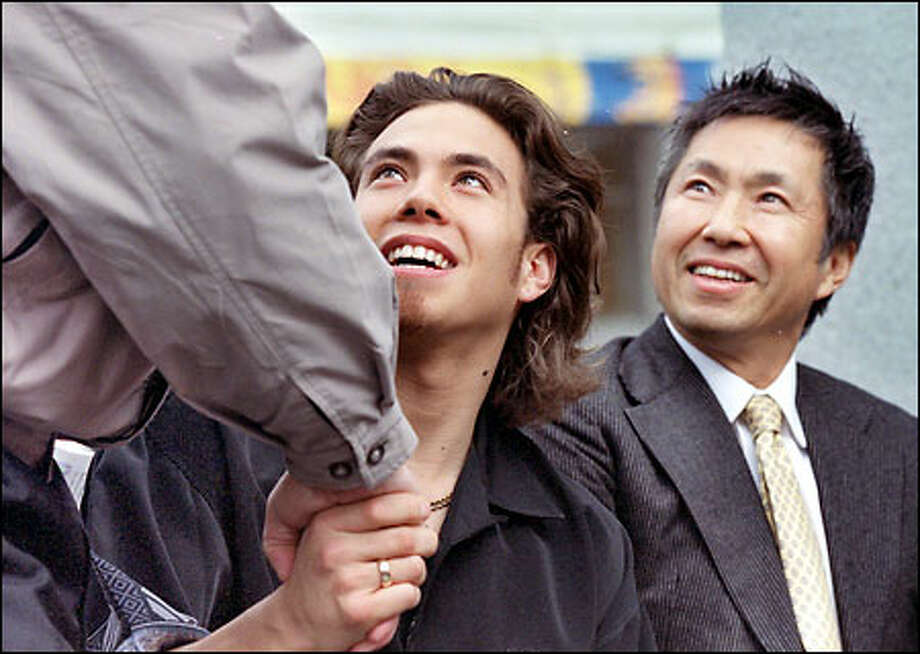 Apolo Anton Ohno and his father, Yuki Ohno, right, are welcomed at the rally in Westlake Park. Photo: Renee C. Byer, Seattle Post-Intelligencer