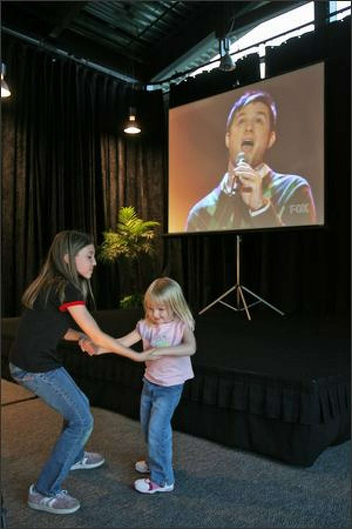 Hannah Kaspar, 9, dances with Ryley Pirak, 3, as Blake Lewis perfoms on American Idol. Supporters of American Idol contestant Blake Lewis gathered at the University of Washington, Bothell, Events Center, near Seattle, Wash., Tuesday May 22, 2007, to watch the final performances via projection television.