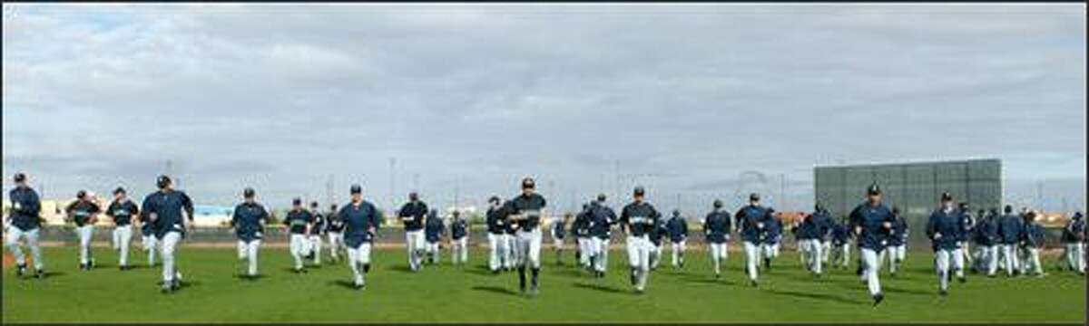 The Mariners take to the field to warm up.