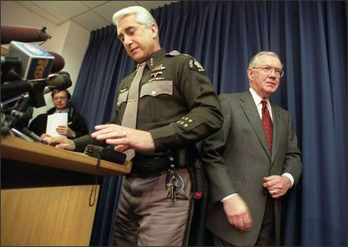 King County Sheriff Dave Reichart, left, takes the podium at a press conference given by King County Prosecutor Norm Maleng, right, after Maleng announced charges against Gary Ridgway. Ridgway was charged with four counts of aggravated murder in the Green River slayings.