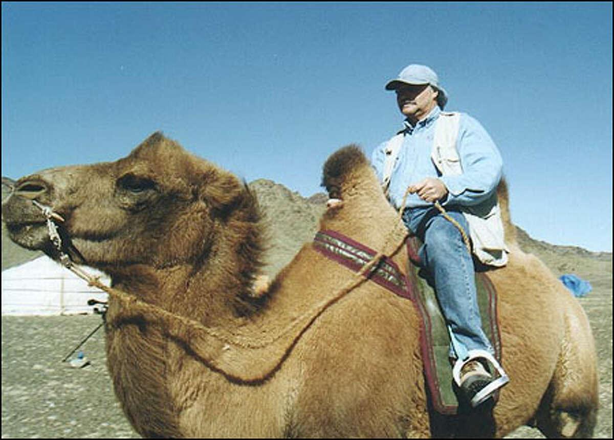 Larry Johnson sitting on a camel.