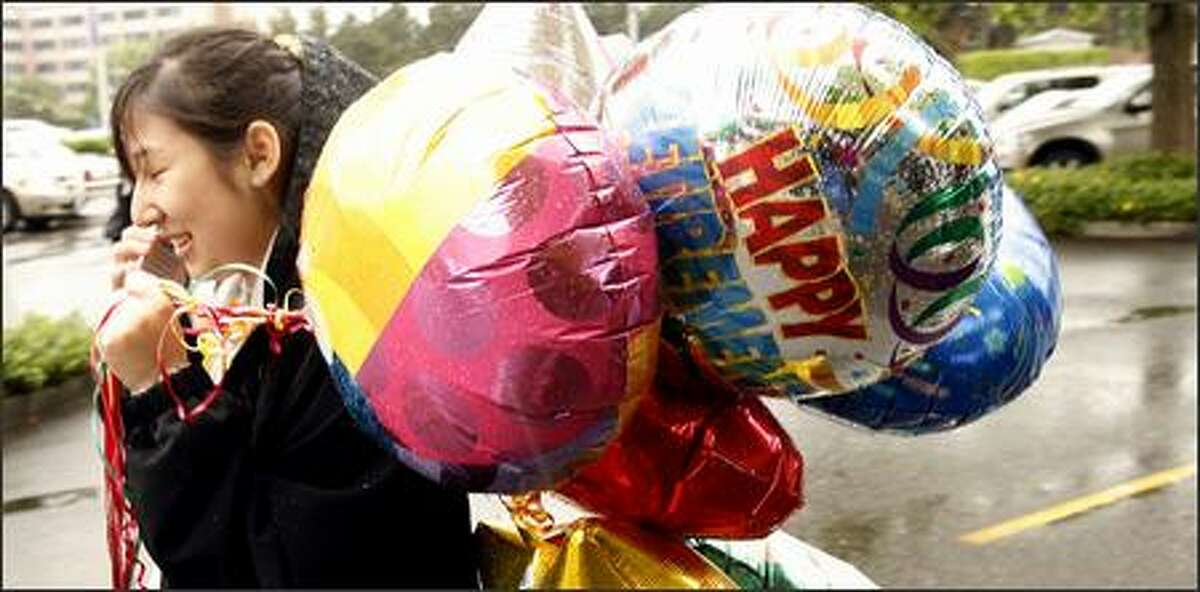 A woman rushes to take balloons, including one bearing the inscription