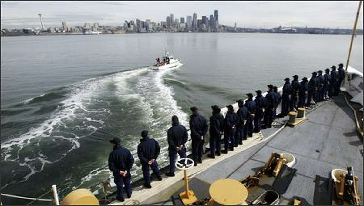 The crew of the USCGC Midgett gather in formation near the edge of the ship as they make their approach to their homeport at Pier 36 in Seattle Friday, March 16, 2007. A coast guard escort leads the way. The 378-foot cutter is completing a six month deployment that included extensive anti-piracy, maritime security and interdiction operations in the Middle East with coalition forces. Midgett then embarked on a global circumnavigation to return to Seattle.