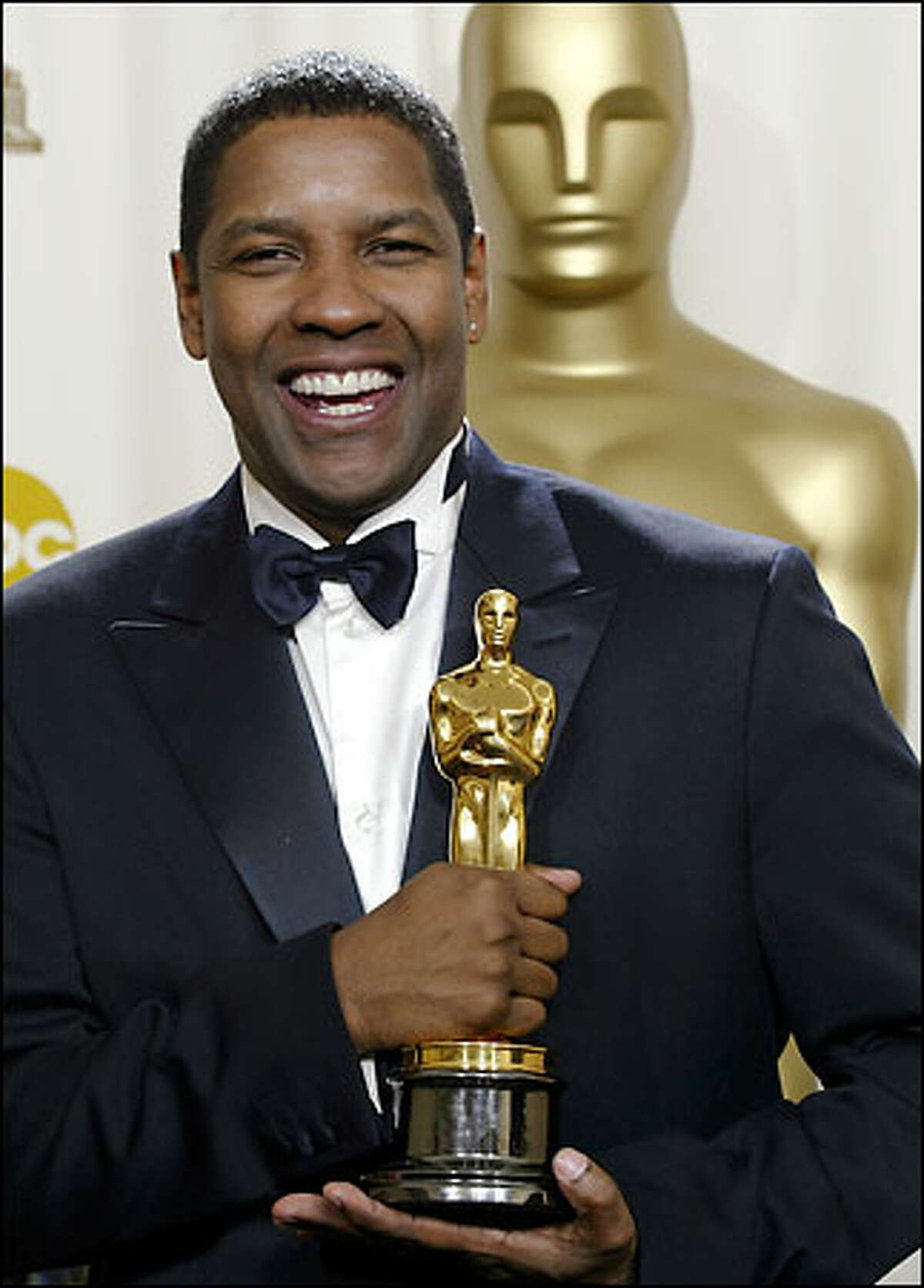 Denzel Washington poses with his Oscar for best actor for his work in the film