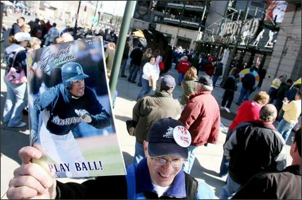 Glen Cook, of Bainbridge Island, sells programs outside Safeco Field as fans show up to see the Seattle Mariners play the Oakland A's on opening day.
