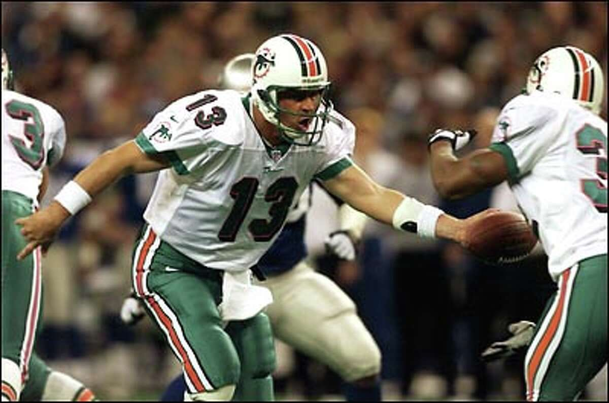 Miami's Dan Marino guides the Dolphins to another playoff victory Sunday. The Seahawks lost their first playoff game in 11 years.