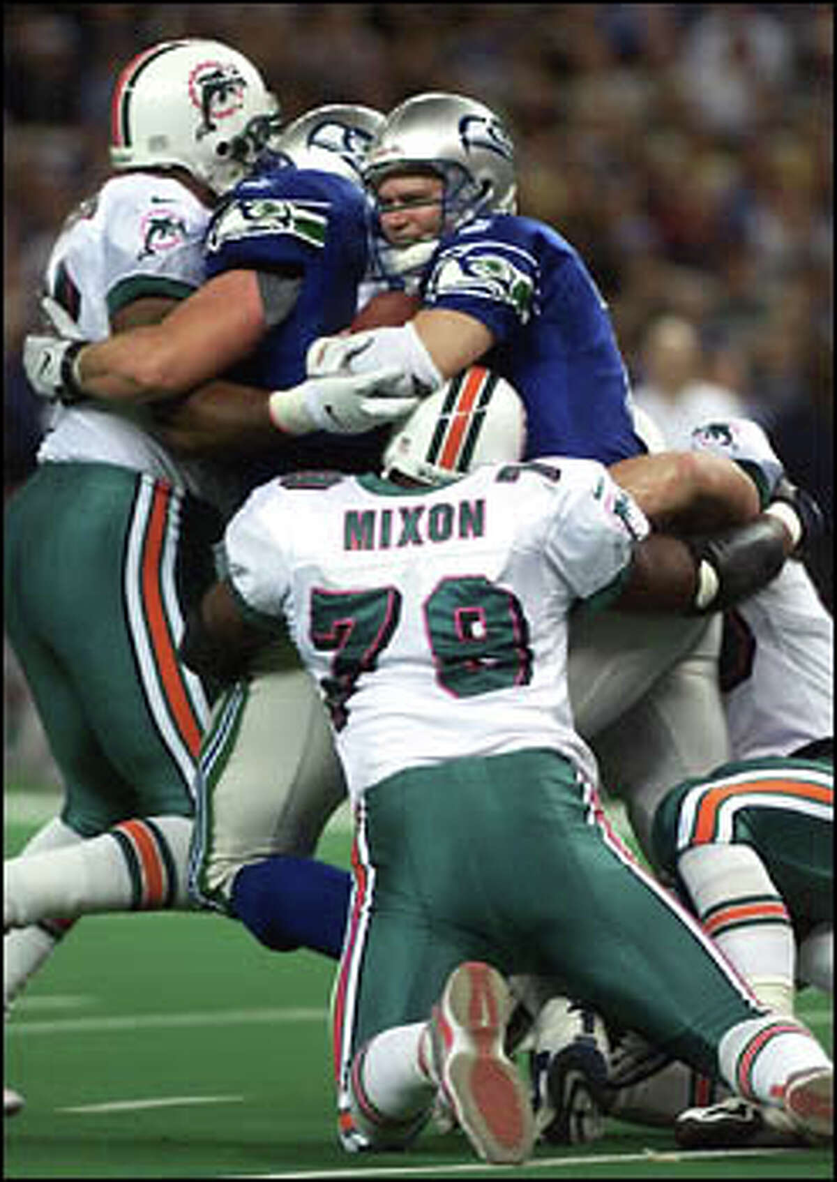 Seahawk QB Jon Kitna is sacked by Dolphin Kenny Mixon and teammates.