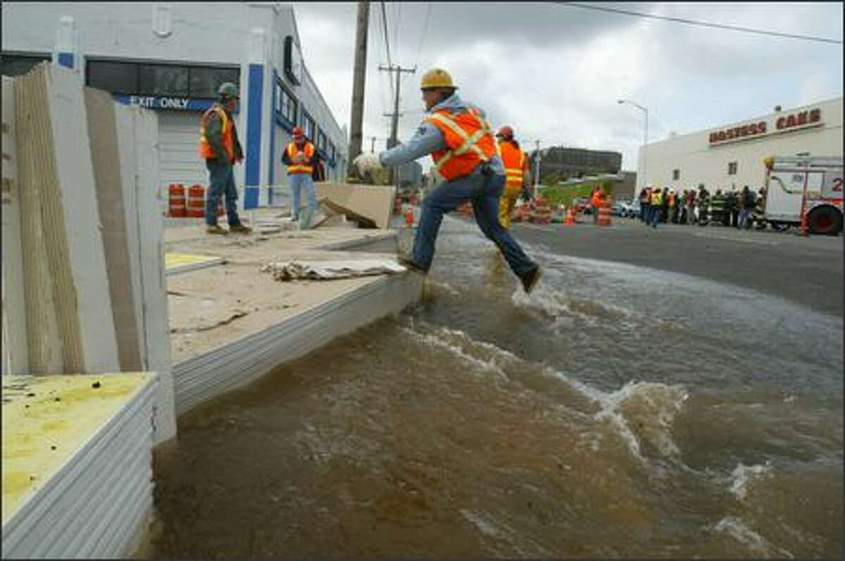 A utilty worker leaps over flowing water to a stack of sheetrock serving as a makeshift sidewalk and dam. A private contractor broke a water main on Dexter Avenue North Wednesday morning, flooding adjacent areas.