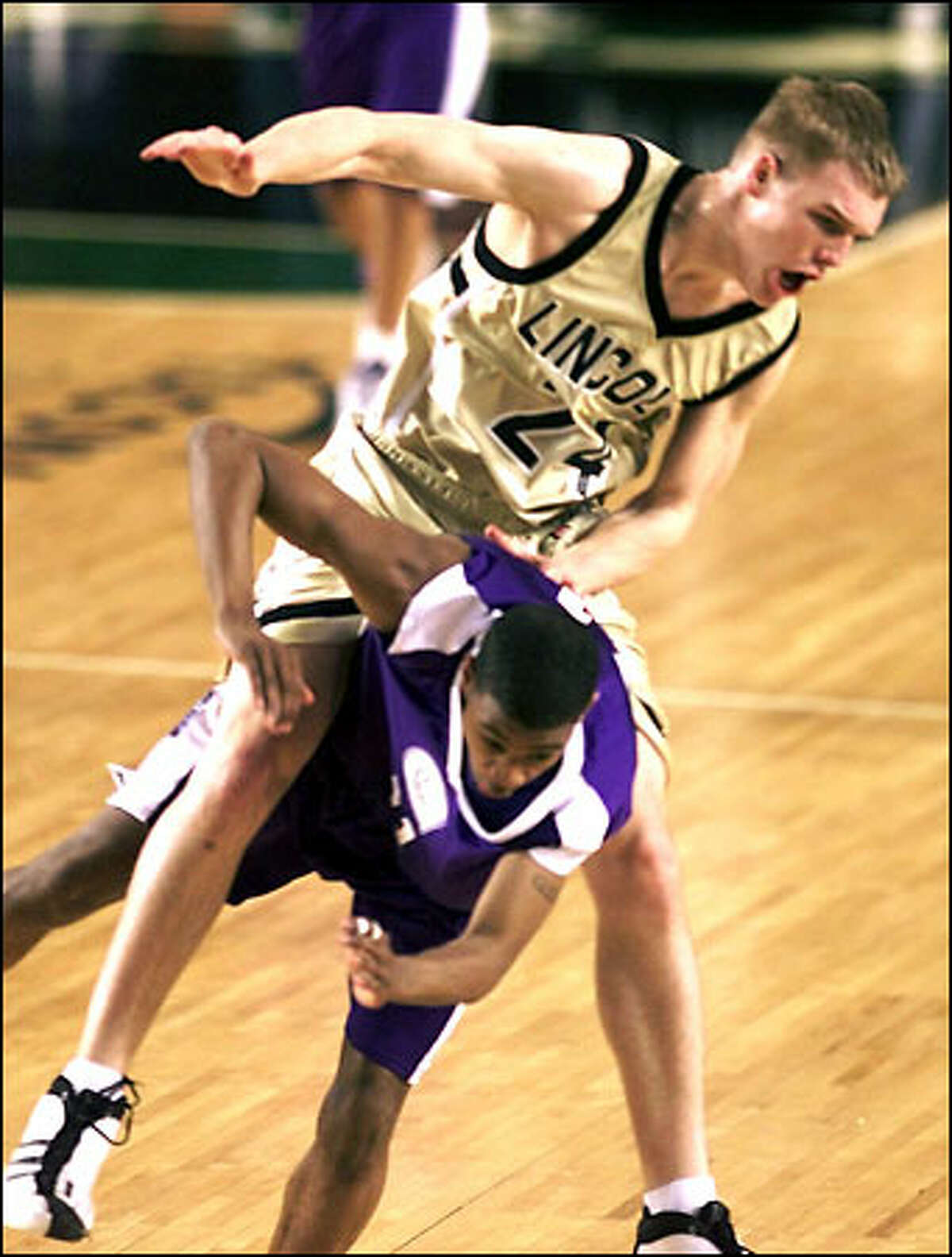 Lincoln's Ben Shelton ends up on top of Garfield's Quinnan Braxton as the pair raced for a errant pass during their playoff game at the Tacoma Dome Thursday March 8, 2002.