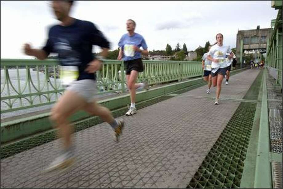 "Runners head across the University Bridge during the 25th  Nordstrom ""Beat the Bridge to Beat Diabetes"" race on Sunday.  More than 9,000 participants took part in the event, which started and ended at Husky Stadium.  The goal of many in the 8K race was to cross the bridge, at the 2-mile mark, before it was raised for 20 minutes. Photo: Karen Ducey, Seattle Post-Intelligencer"