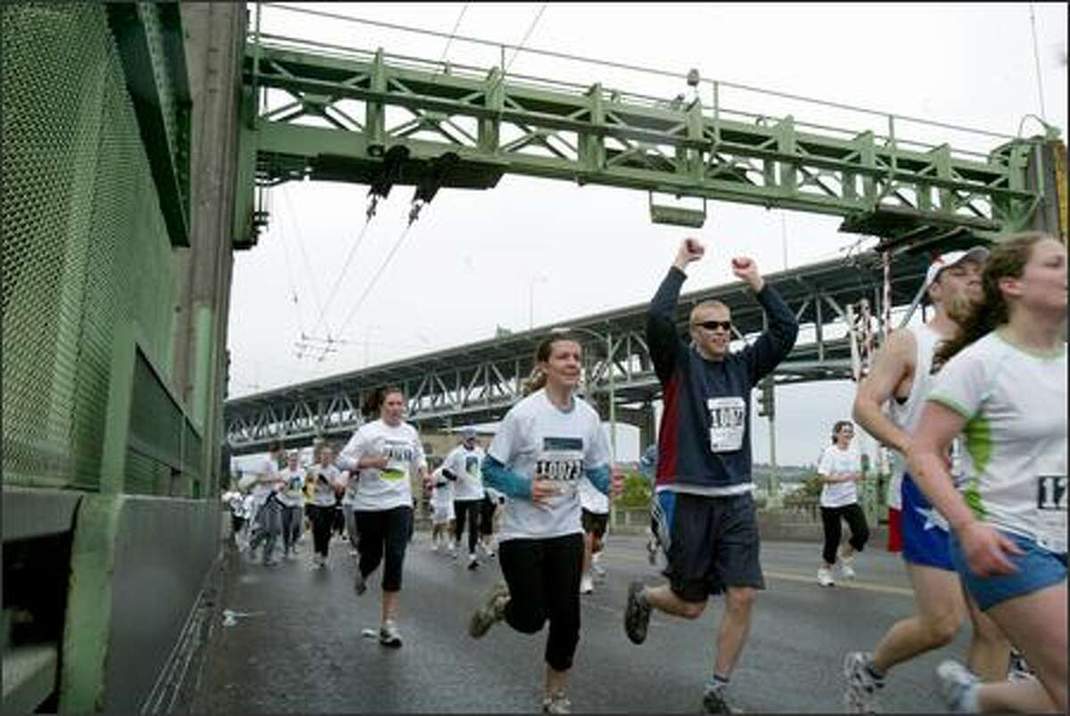 Runners triumphantly cross the University Bridge seconds before it is raised during the 25th Nordstrom