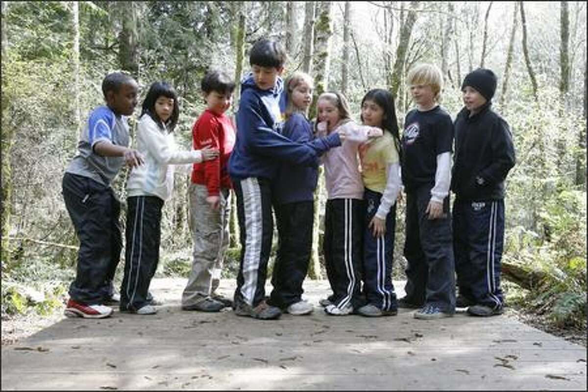 Fifth grade students from Catharine Blaine Elementary School in Seattle work together to balance themselves on a balance board as they participate in a team building exercise at IslandWood Camp on Bainbridge Island on Wednesday March 28, 2007.