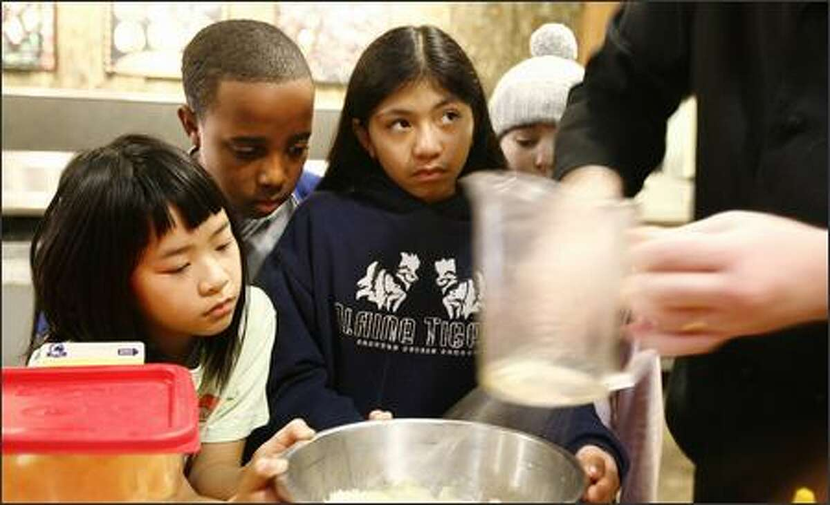Students from Catharine Blaine Elementary School in Seattle participate in a cooking class at IslandWood Camp on Bainbridge Island on Wednesday March 28, 2007. Students Cayla Chow 10, Hiawatha Davis 10, Makara Montes 10, and Maddy Blue 11 watch as camp cook John Lynch mixes up a batch of ranch dressing for their lunch. IslandWood is an overnight science-education camp for 4th,5th,and 6th graders, which regularly hosts students from Seattle public schools. Students visit the camp for four days to learn about science, nature and the environment. It's sort of like 'outdoor school', a way to get kids from urban schools to connect with nature.