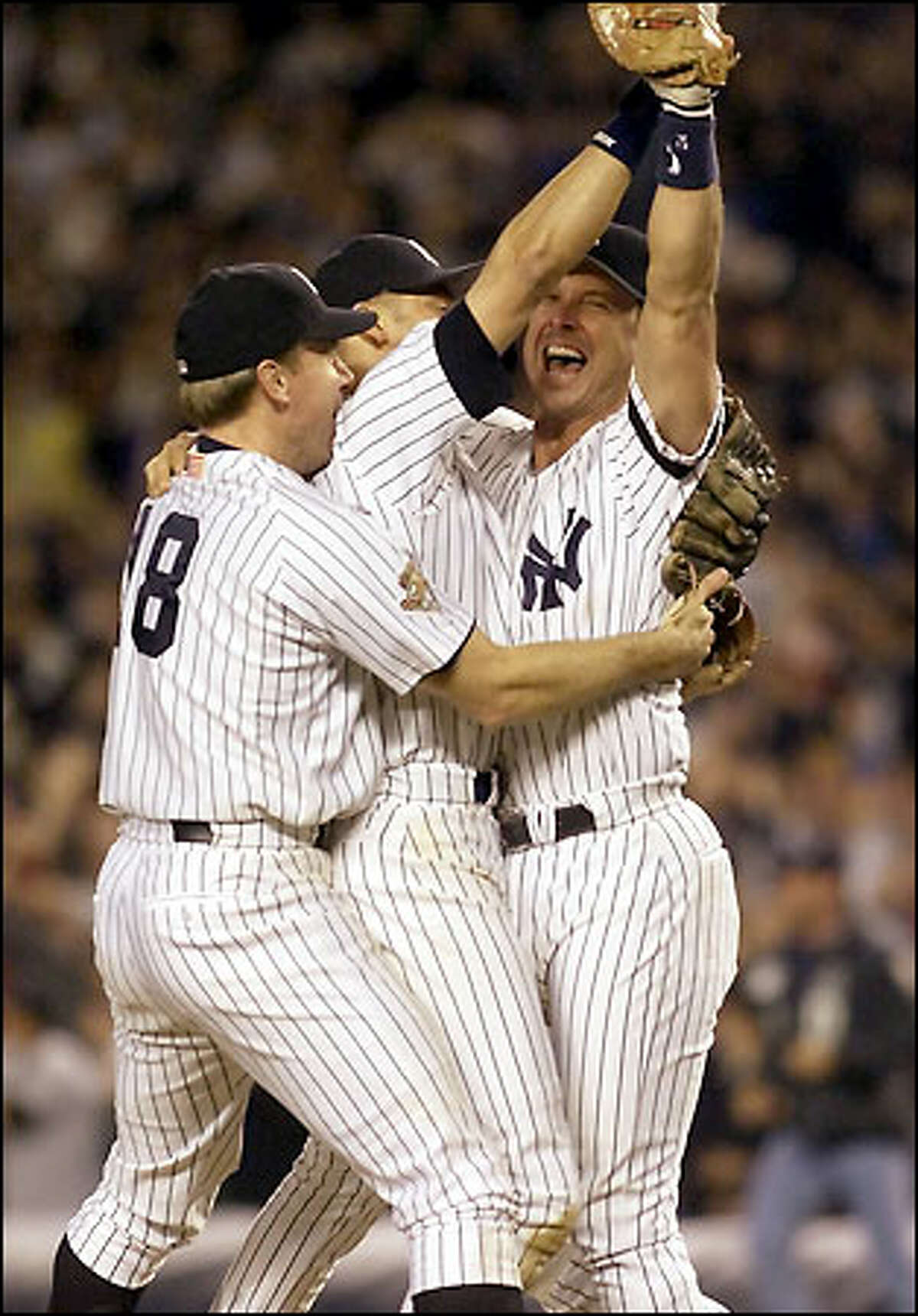In an all-too-familiar scene for Mariners fans, Yankees players, from left, Scott Brosius, Derek Jeter and Tino Martinez celebrate a clinching victory over Seattle. The Yankees have stopped Seattle one series short of the World Series the past two seasons.