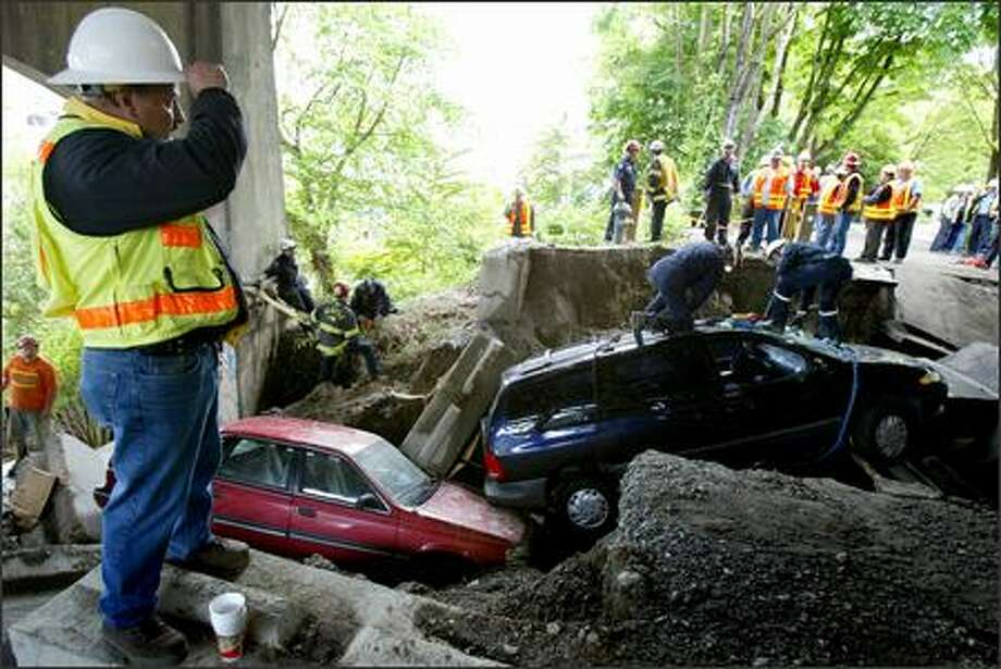 Workers prepare to remove two cars, one resting atop concrete and a gas main, after a broken water main underneath the University Bridge took out a road and swallowed the two cars in Seattle on Wednesday. Photo: Joshua Trujillo, Seattlepi.com