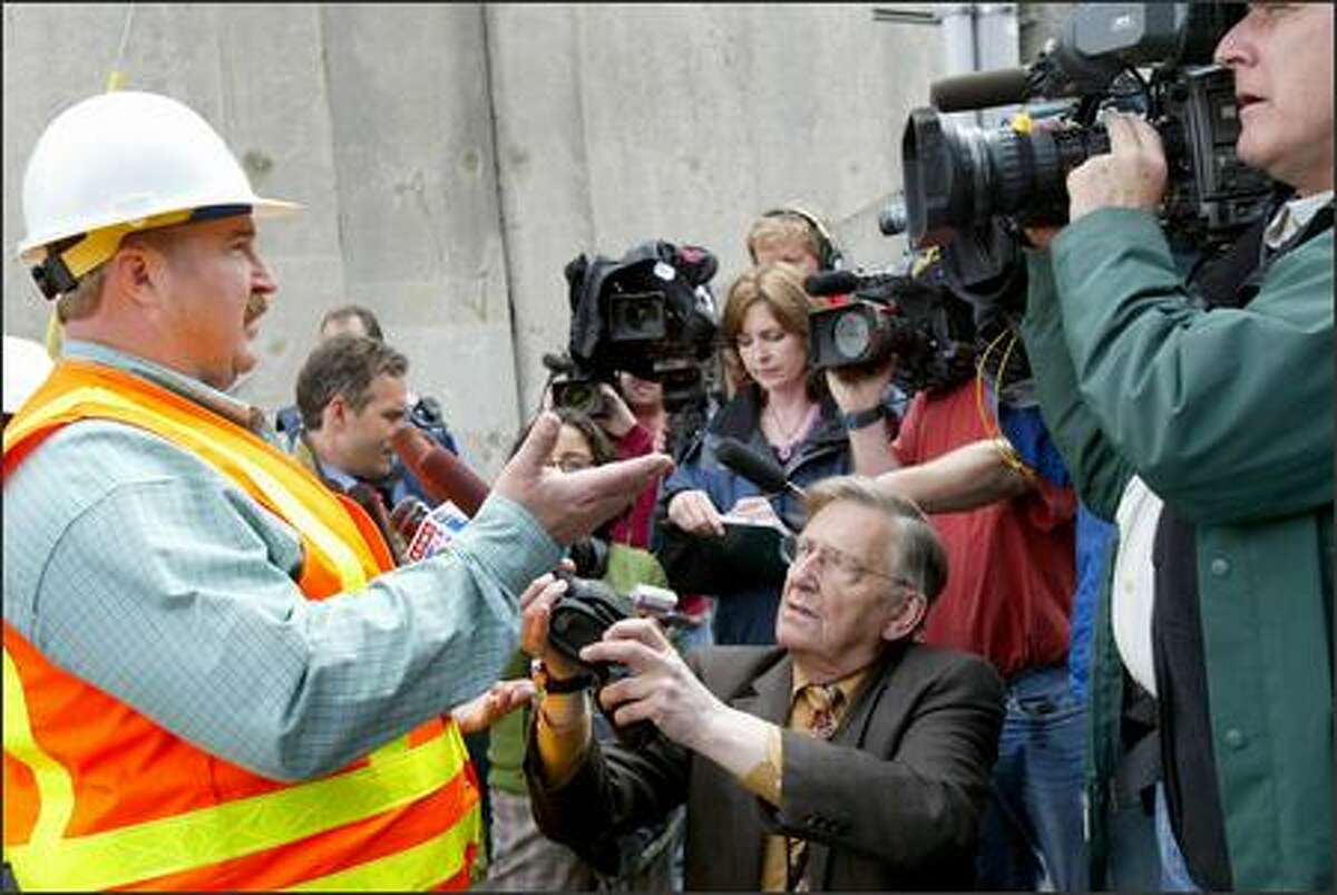 Joe Mickelson, a Seattle Public Utilities official, speaks to the media after a broken water main underneath the University Bridge in Seattle on Wednesday caused a large sinkhole and landslide.