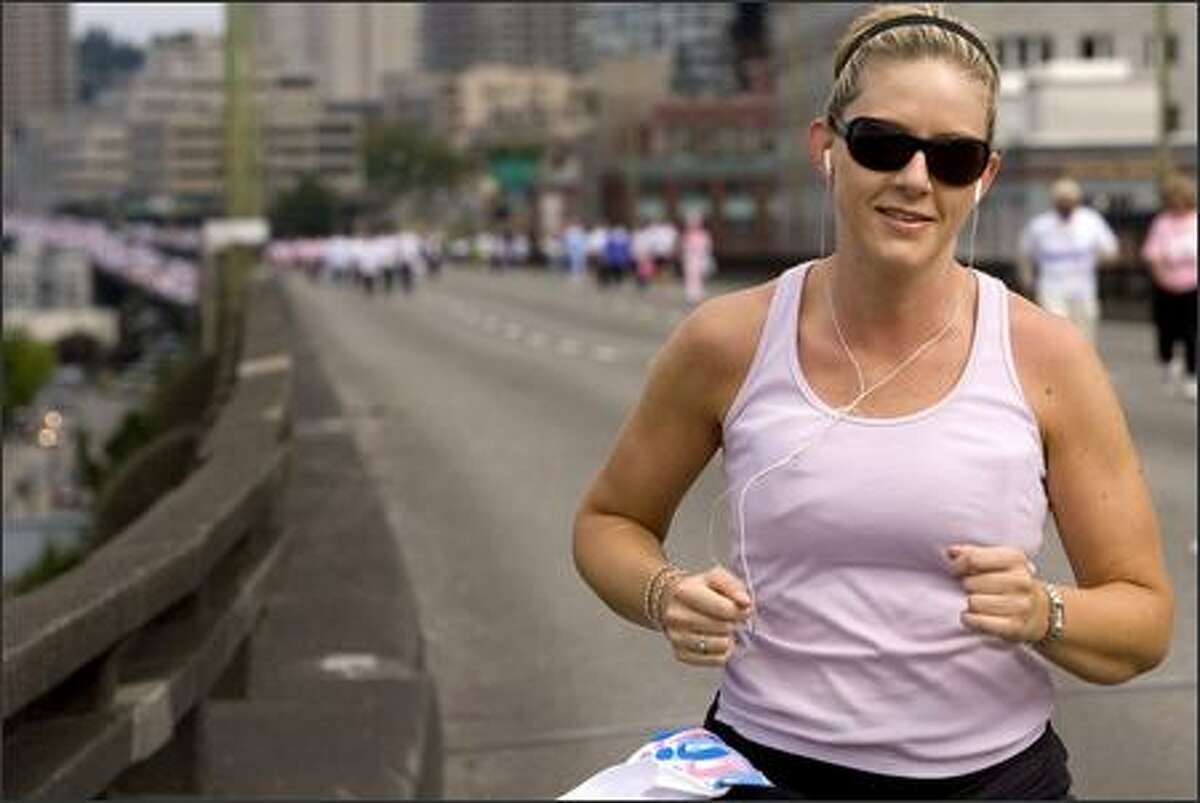 """Andrea DeVry was ahead of a group of more than 13,000 walkers as she ran south in the northbound lanes of the Alaskan Way Viaduct during the Susan G. Komen """"Race for the Cure."""""""