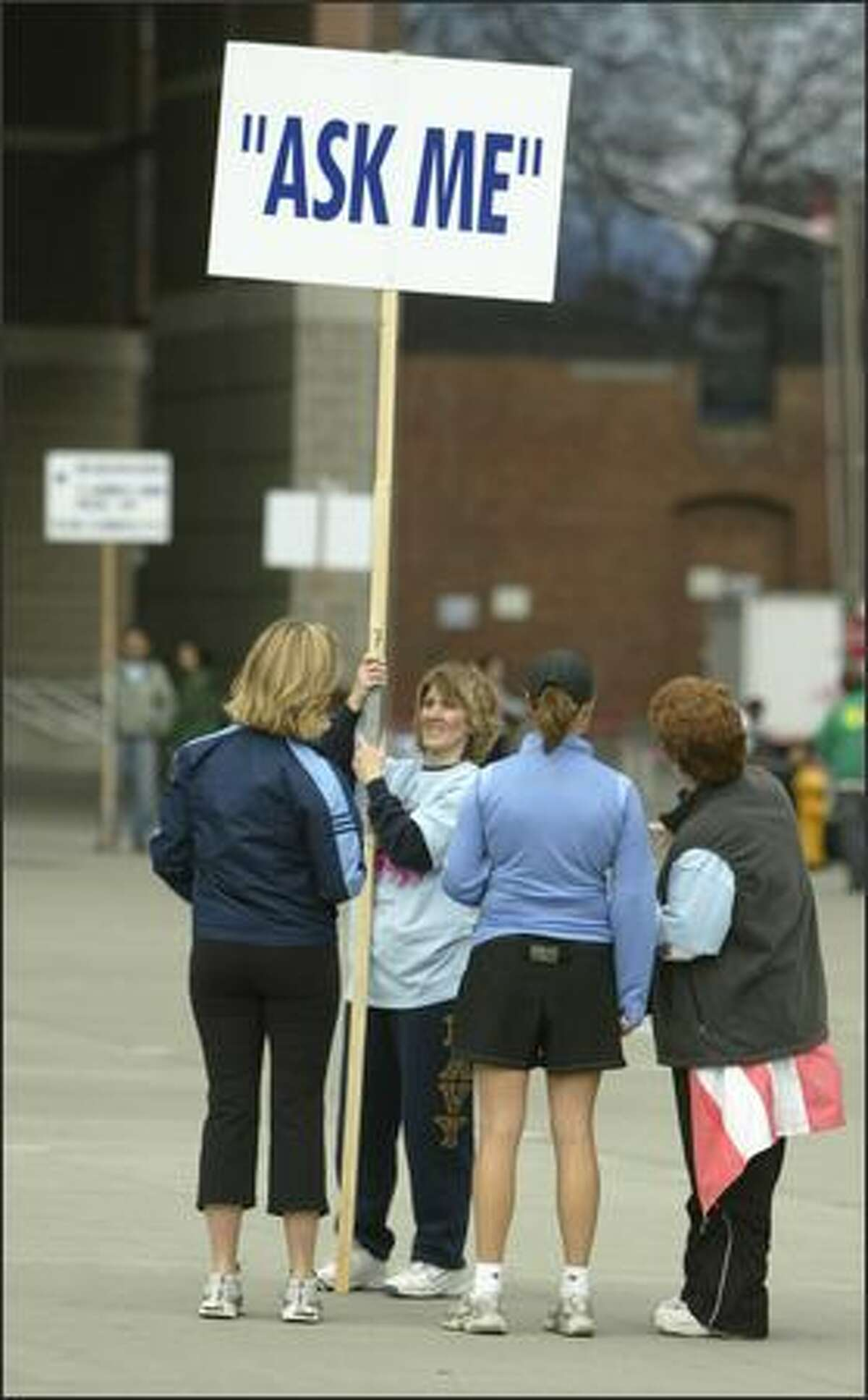 Volunteers Cindy Evans, holding sign, and Kass Klemz, right, give directions to early arriving runners in front of Qwest Field.