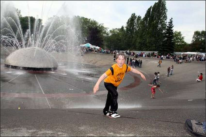Devin Mays, a second-grader from Burien, scales up the International Fountain during the Northwest Folklife Festival Saturday at Seattle Center.