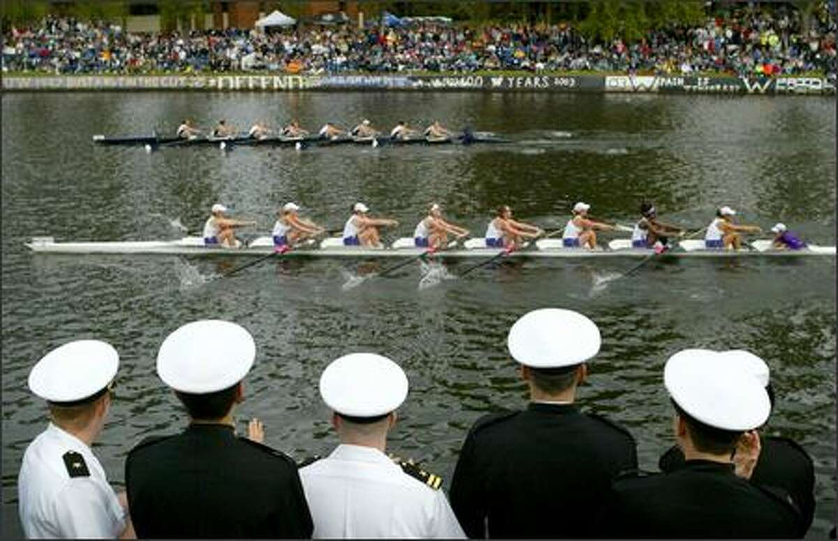 University of Washington Navy ROTC members watch as the UW women's team pulls for the Erickson Cascade Cup during the Windemere Cup races through the Montlake Cut.