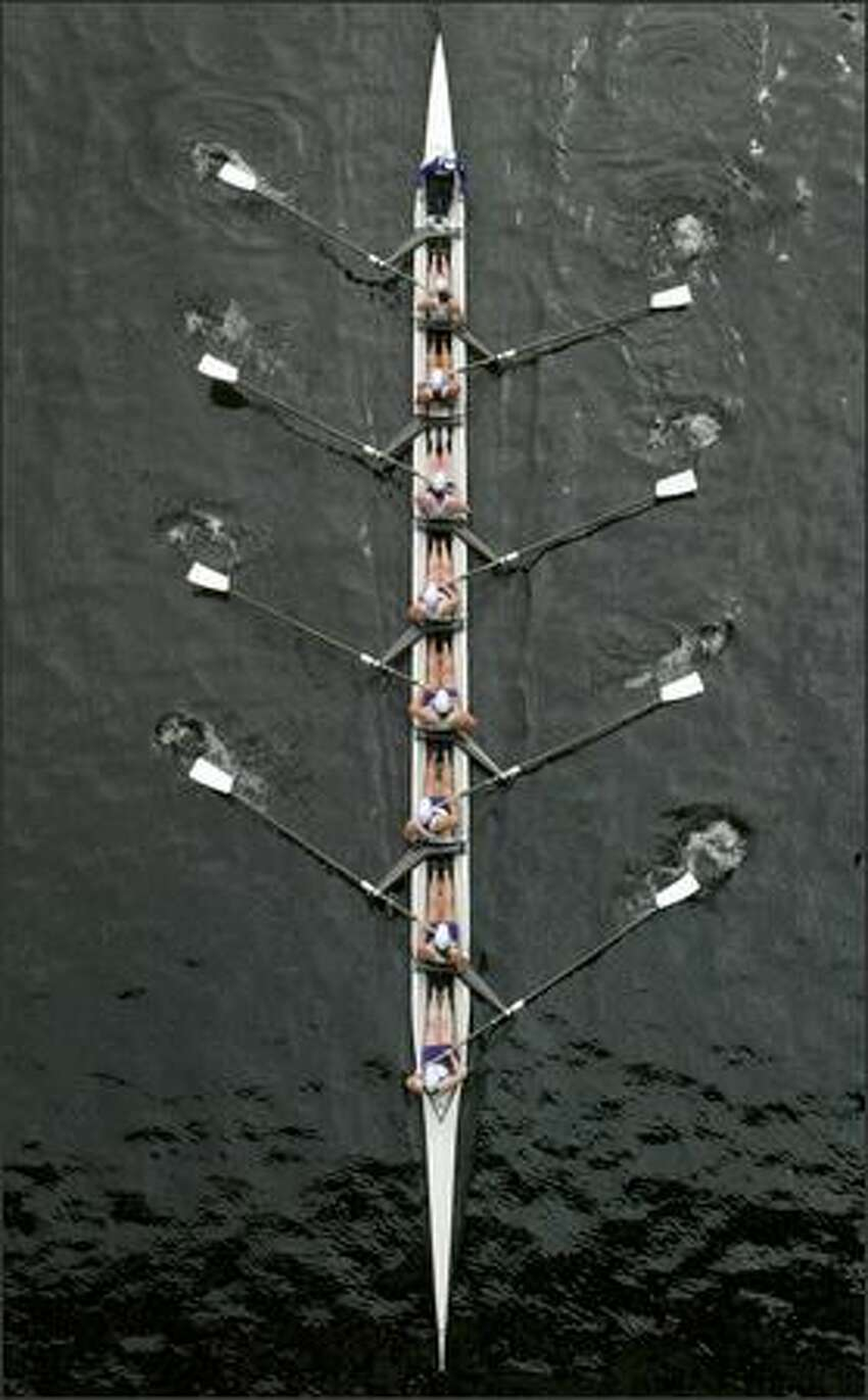 Female racers compete in an early women's 8 event during the Windemere Cup races through the Montlake Cut.