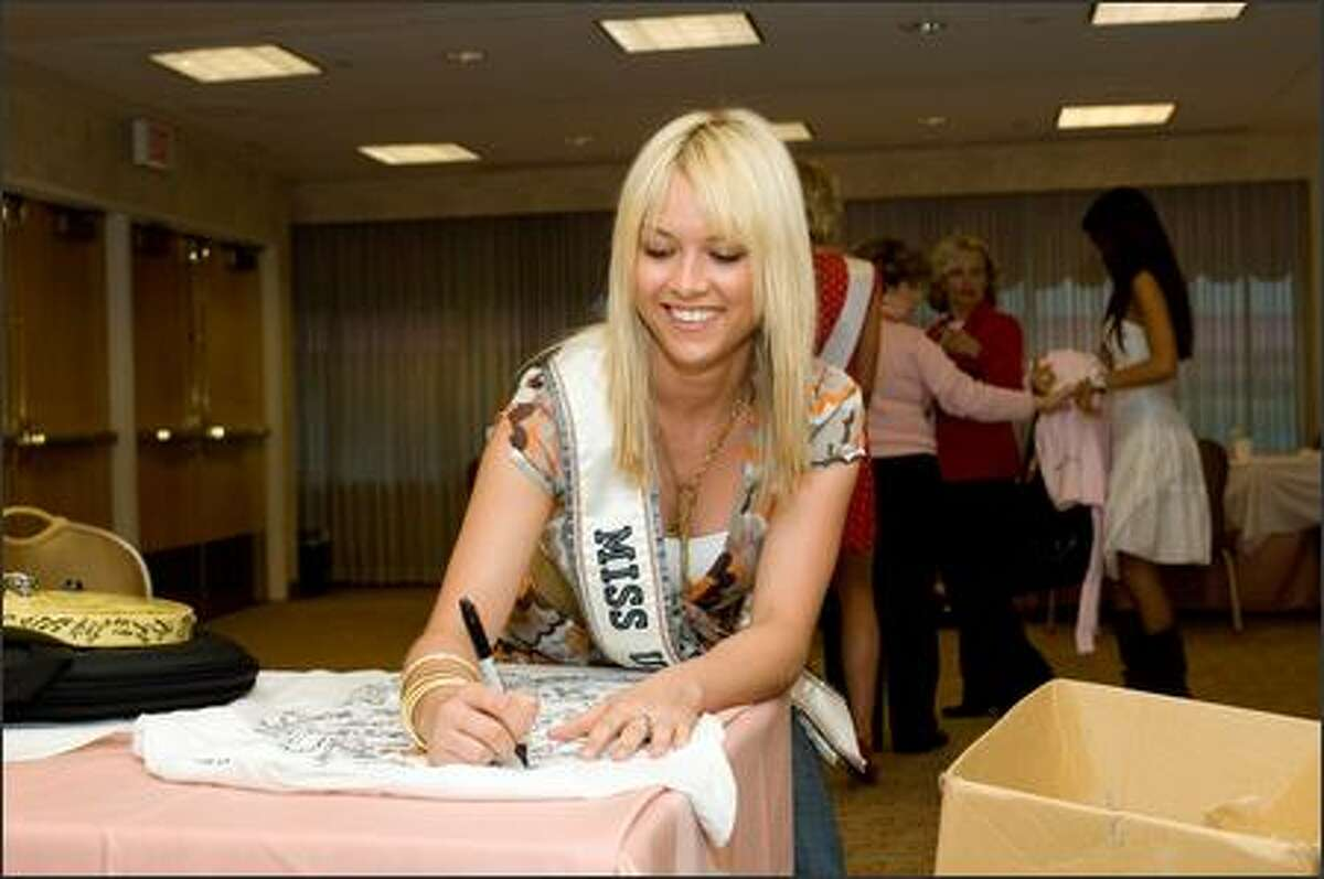 Tara Conner, Miss USA 2006, signs a shirt that will be auctioned from the Hard Rock Cafe.