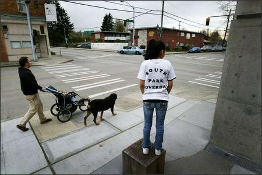 Karina Ruiz, 14, stands on a post in front of the new South Park branch of the Seattle Public Library. The new library was built on the spot where a local neighborhood boy was killed in a drive-by shooting nearly two years ago.