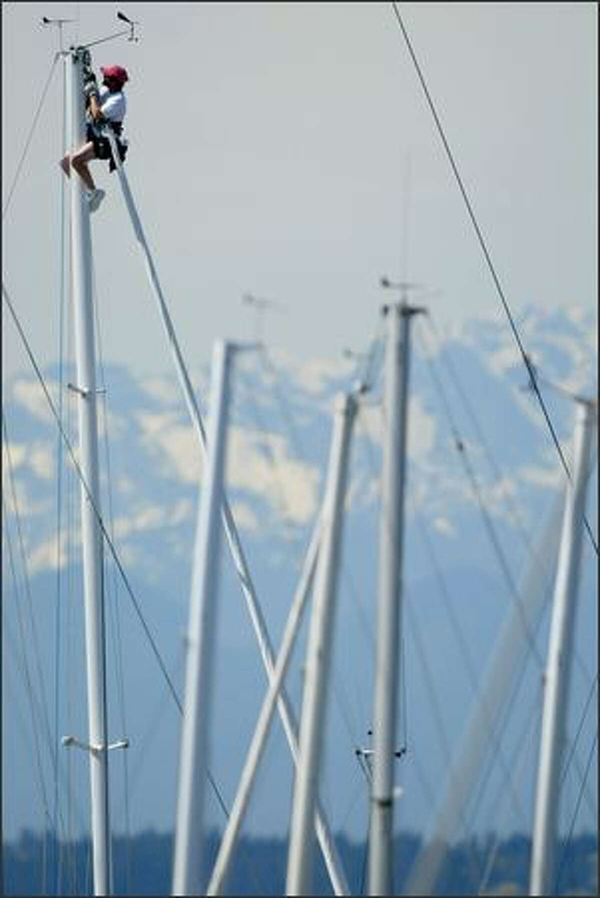 Dave White takes advantage of warm weather and is hoisted up the mast while he works on the rigging of the sailboat Kaulana at Shilshole Bay Marina in Ballard on Friday in Seattle. The Olympic Mountians are seen in the background.
