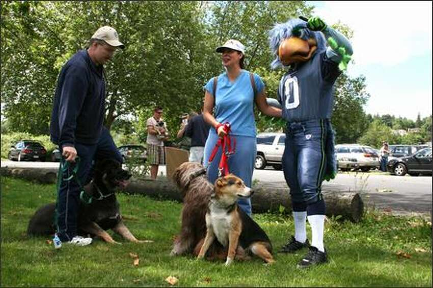 Two dog owners exchange jokes and pose with Seahawks mascot Blitz.