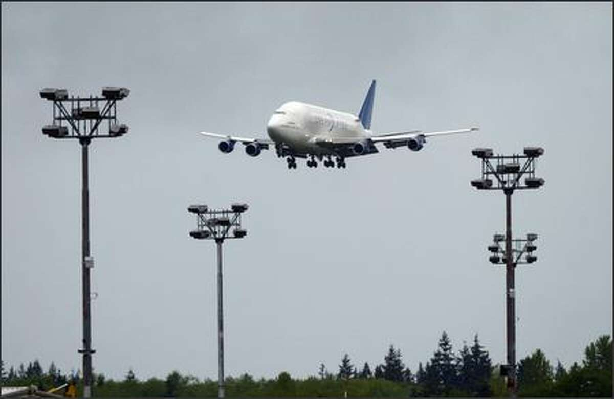 A modified 747 lands ferrying a horizontal stabilizer for the new Boeing 787 Dreamliner from Italy, the first component transported to Boeing's Everett plant on Tuesday at Paine Field in Everett.