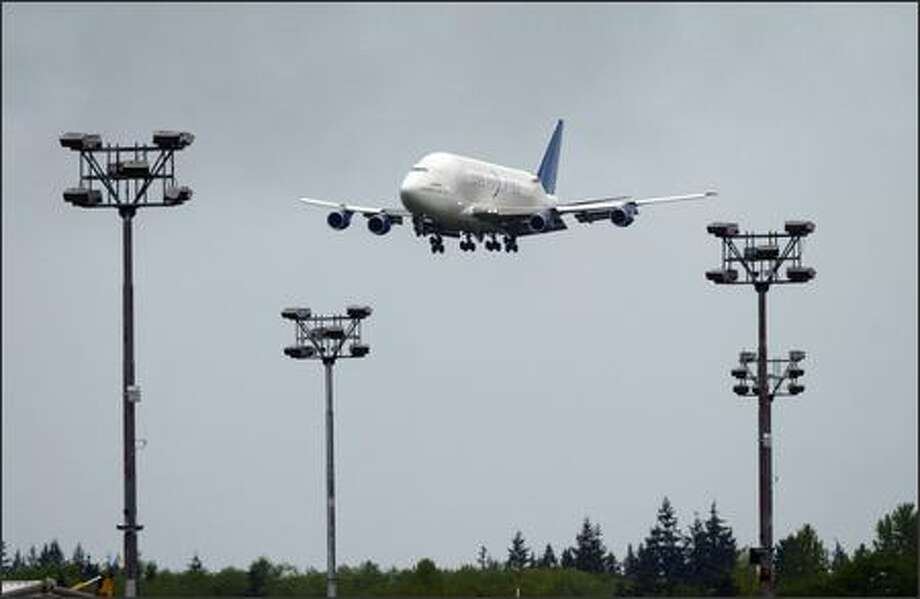 A modified 747 lands ferrying a horizontal stabilizer for the new Boeing 787 Dreamliner from Italy, the first component transported to Boeing's Everett plant on Tuesday at Paine Field in Everett. Photo: Joshua Trujillo, Seattlepi.com